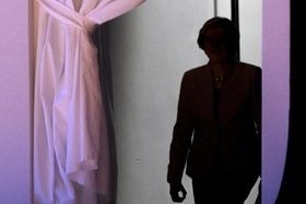 British PM Theresa May in the shadows by a curtain