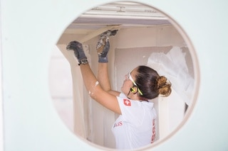 A woman plasters a ceiling