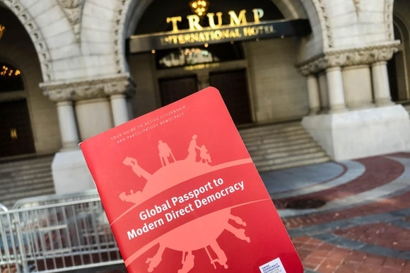 Global Passport to Modern Democracy held against the background of the Trump International Hotel