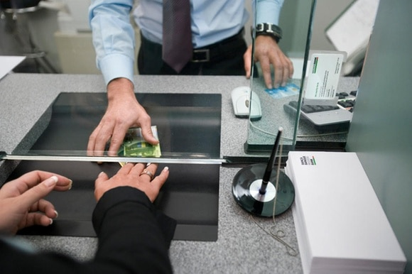 A bank cashier hands money over to a customer