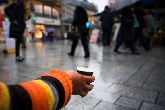 A beggar holds out a hand with a cup for putting money