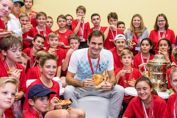 Roger Federer surrounded by pizza-eating ball boys and girls