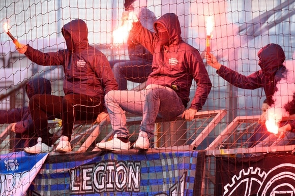 Masked football fans wave flares at a match in Lausanne