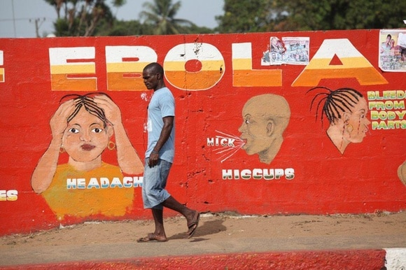 A Liberian man walks pass an Ebola awareness mural in downtown Monrovia, Liberia in 2015