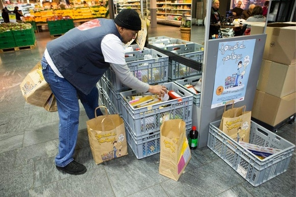 man packing crates of food