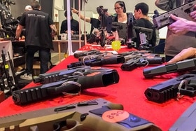 Gun fans check out new weapons at a stand at the 24th International Gun Fair in Lausanne