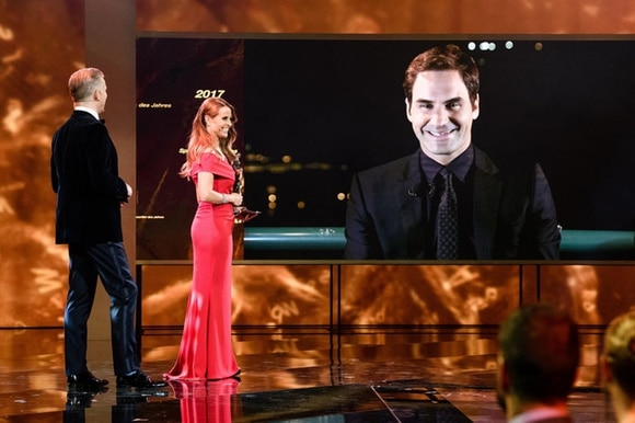 Roger Federer on a screen accepting his award