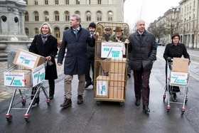 Proponents of a Swiss people s initiative bring boxes of signatures to submit in Bern