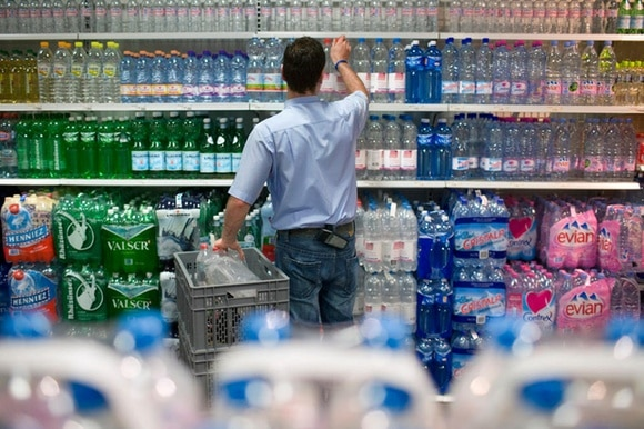 An employee stocks bottled beverages in a Swiss supermarket