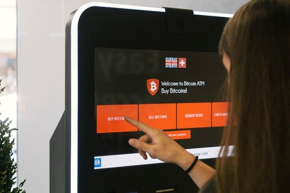 A woman buys bitcoin from an atm in Switzerland