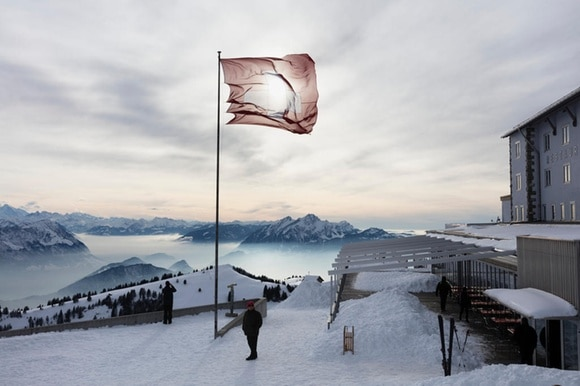 A Swiss flag blows in the wind on top of a snowy mountain peak