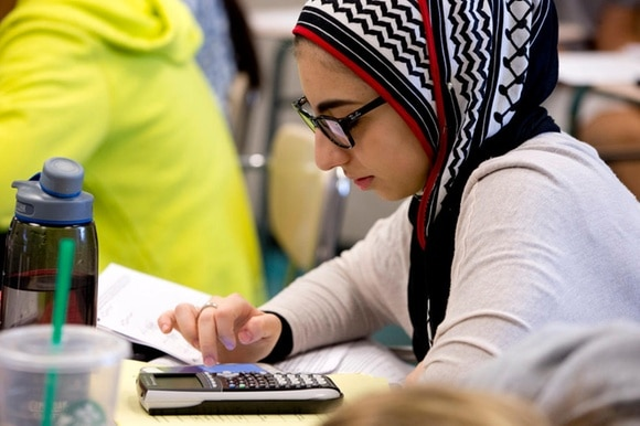 A girl wearing a headscarf uses a calculator