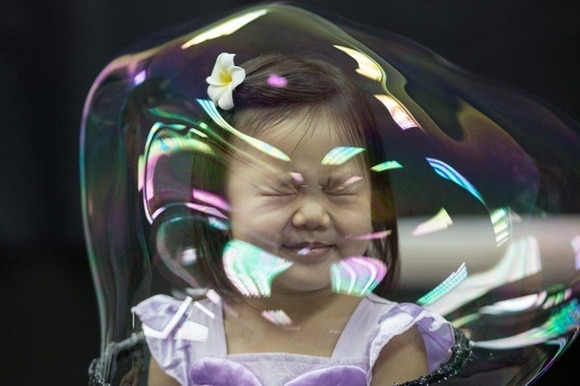 A girl grimaces with her head in a bubble