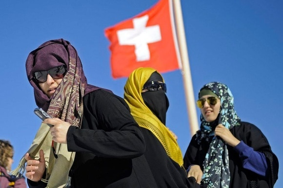 Three women wearing headscarves under a Swiss flag