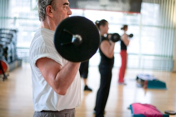 Scene from a fitness studio: man lifting a bar bell