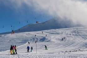 People skiing on wide slopes, with a chairlift in the background