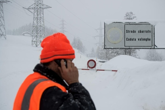 Road blocked by snow and roadworker on phone