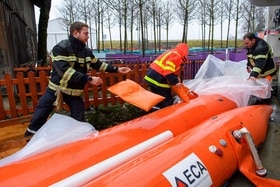 Emergency services blow up rubber tubes to damn river banks