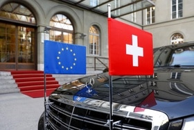 A car sports the flags of the EU and Switzerland