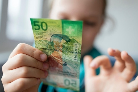 A child holds a 50 franc note