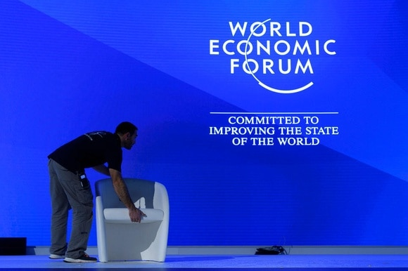 A person places a chair on a stage lit up by the World Economic Forum logo