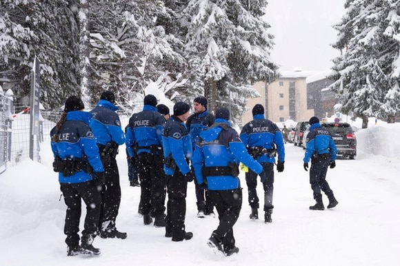 blue-clad police on snow-covered road