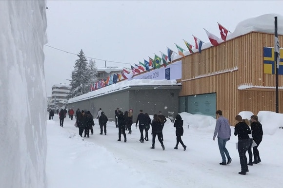 people traipsing through snow to conference
