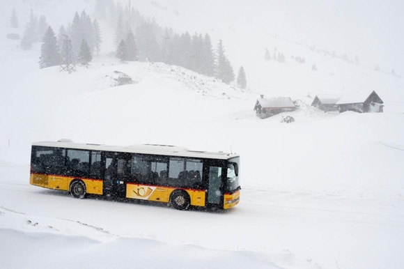 A PostBus drives through the snow