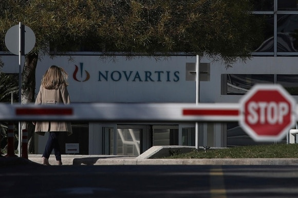 A woman enters Novartis Greek offices in Athens, on Tuesday, Feb. 6, 2018.