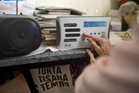 portable radio on a shelf, hand of and elderly person pushing a button