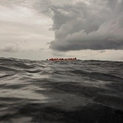 Libyan migrants in a boat at sea wait to be rescued by aid workers of the Spanish NGO Proactiva Open Arms