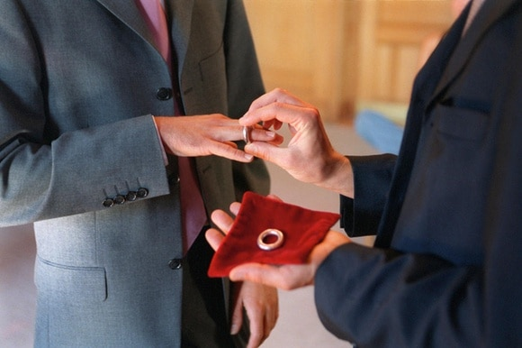 A picture of a gay couple exchanging rings in a civil partnership ceremony