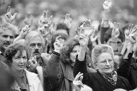 Black and white archive photo of women and men holding up their hands to vote