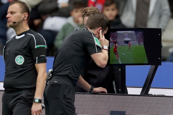 A referee consults a video during a Bundesliga match in Germany