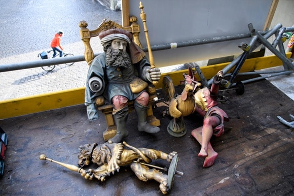 Figures of Chronos, a lion and Joker lie on the scaffold floor, Below a cyclist drives by.