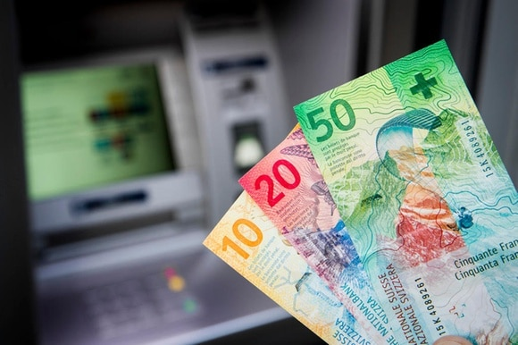 Swiss franc bank notes and a cash machine