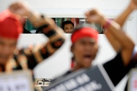 A military guard watches as Filipino indigenous people raise their clenched fists during a rally