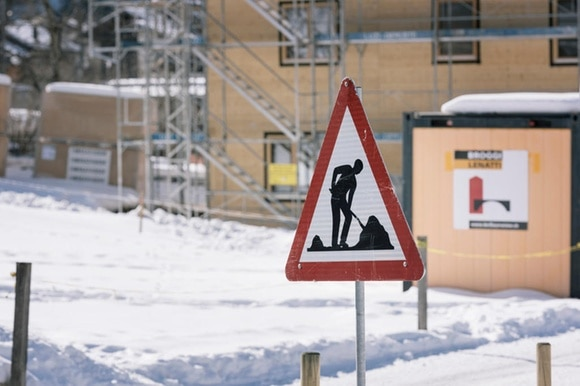 A building sign outside of a snowy construction site