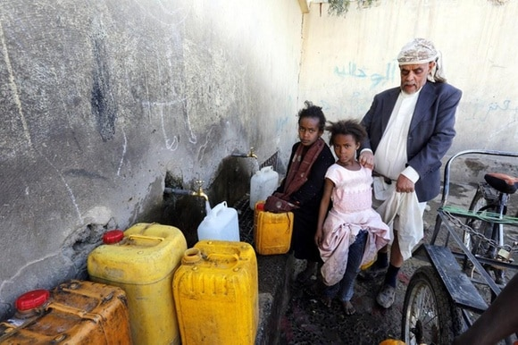 Yemenis fill jerrycans with drinking water from a donated water pipe in the capital Sana a.