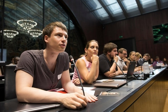 young people sitting at a table in a committee room in the Swiss parliament building