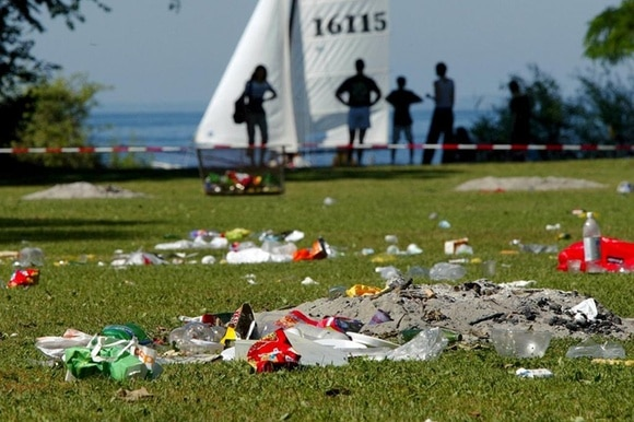 Pile of rubbish on grass in front of a lake and sailing boats