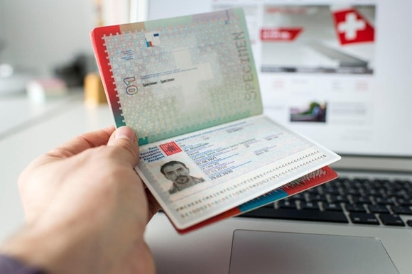 A Swiss biometric passport is held open to the ID photo page