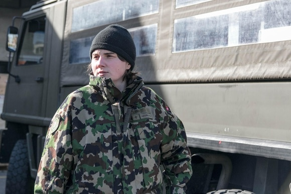 Private Zoé in front of a military vehicle