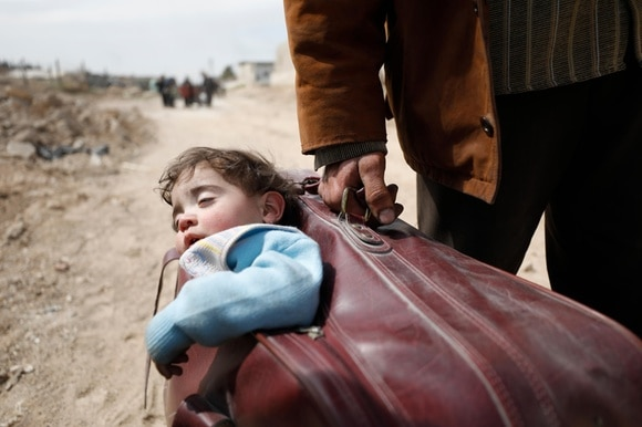 A child carried in a suitcase in Syria