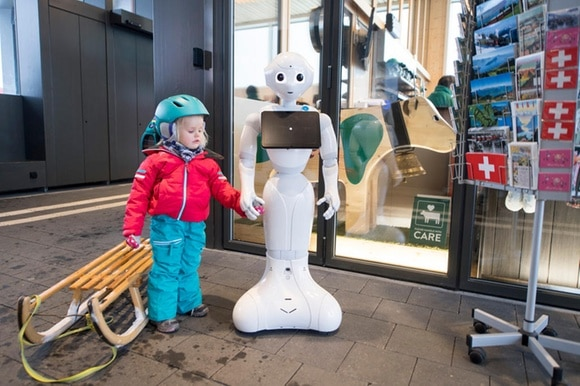 Young girl holds a robot s hand