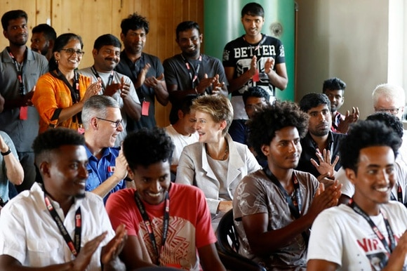 Asylum-seekers clapping during a workshop