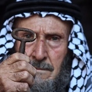 Elderly Palestinian man holds a key symbolizing the right of return of Palestinian refugees