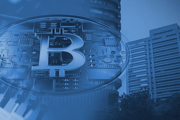 A bitcoin symbol superimposed against a backdrop of buildings