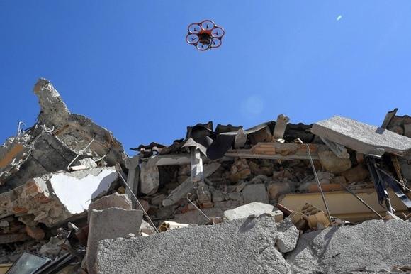 A drone flies over the debris of Amatrice school, central Italy, Friday, Sept. 2, 2016 following an earthquake