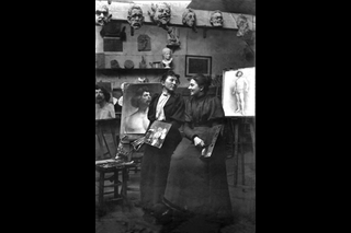 Photograph of Alice Dannenberg und Martha Stettler standing in front of portraits of men.
